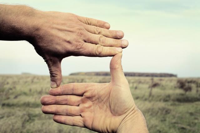 Image of two hands framing landscape composition